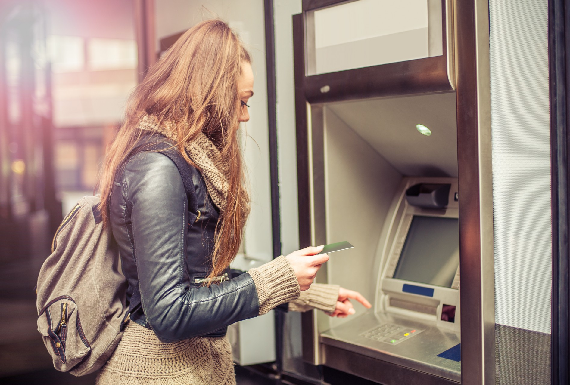Young woman withdrawing money from debit card at ATM